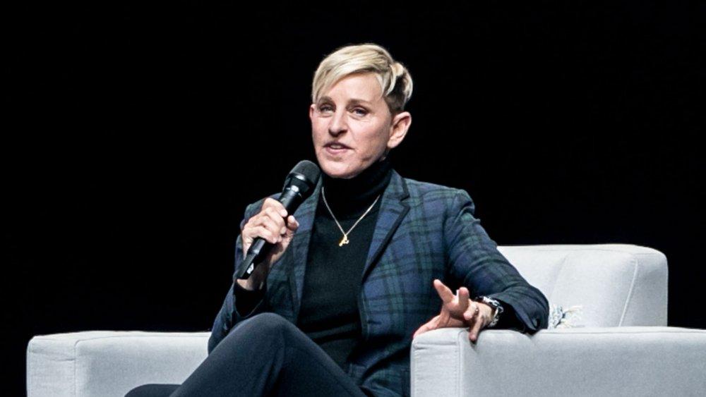 Ellen DeGeneres dans un costume à carreaux bleu, assis et parlant dans un micro