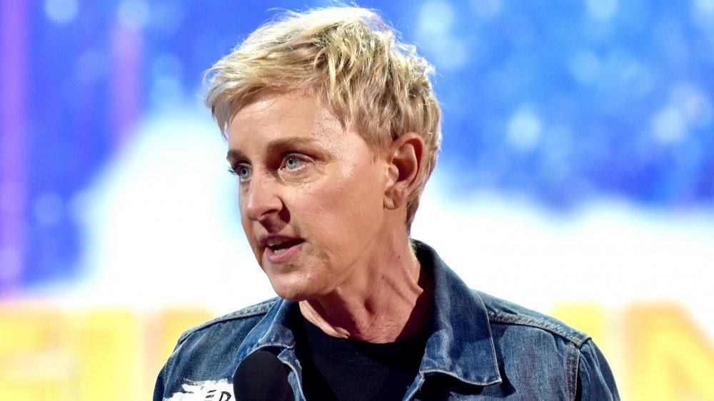 Ellen DeGeneres dans une veste en jean, parlant dans un micro avec une expression intense