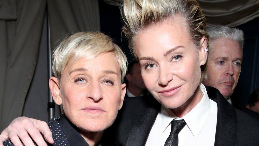 Ellen DeGeneres en costume bleu à pois, Portia de Rossi en costume noir et cravate, posant les bras autour de l'autre