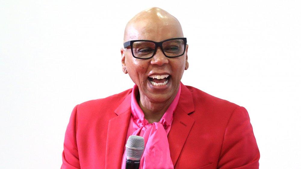 RuPaul riant dans la tenue rouge et rose