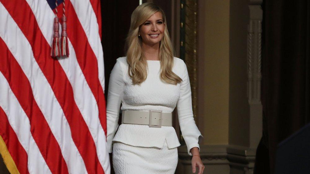 Ivanka Trump souriant dans une tenue blanche tout en marchant par le drapeau américain