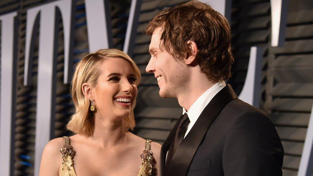 Emma Roberts dans une robe d'or et Evan Peters dans un costume noir, souriant les uns aux autres sur le tapis rouge