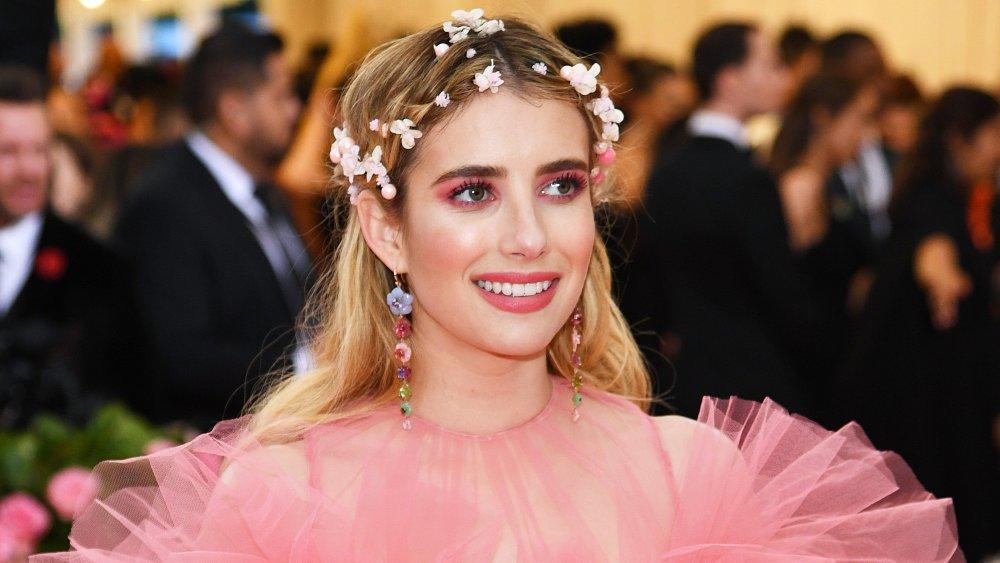 Emma Roberts dans une robe rose et couronne de fleur, souriant