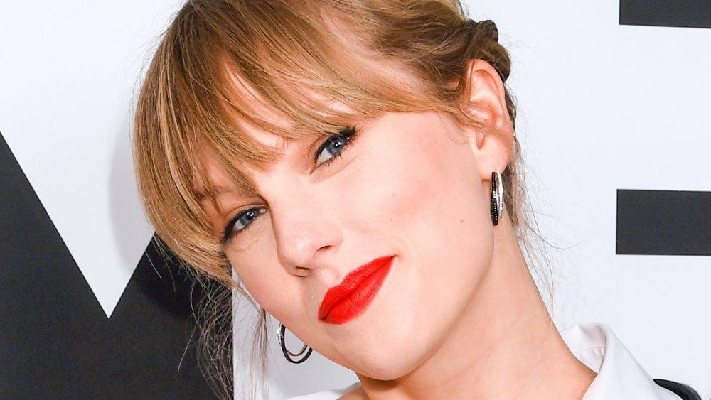 Taylor Swift sourit en penchant la tête