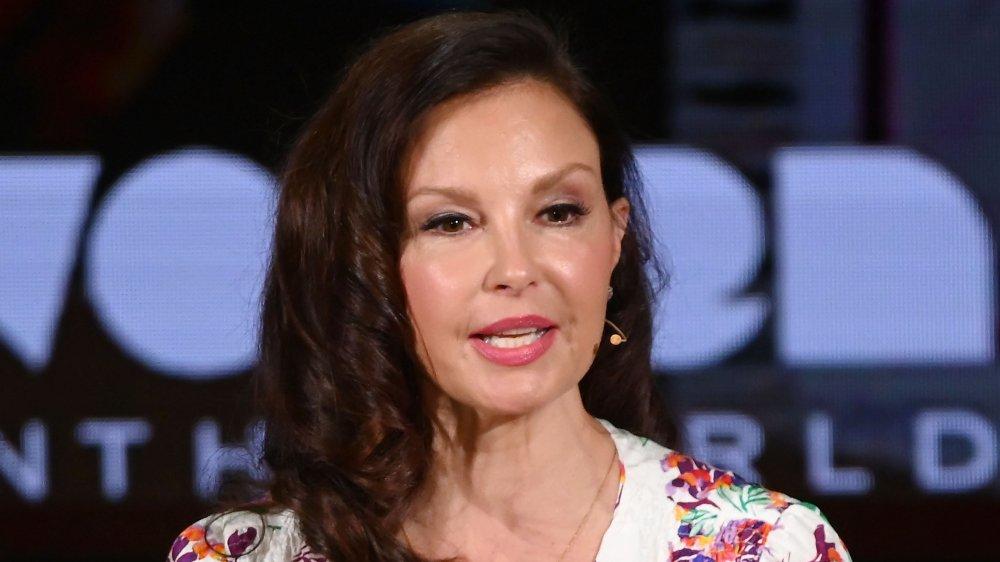 Ashley Judd dans une robe blanche à imprimé floral, parlant avec ses mains lors d'un événement