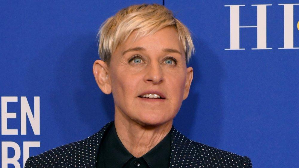 Ellen DeGeneres en costume à pois bleu et chemise noire, posant avec une expression neutre aux Golden Globes 2020