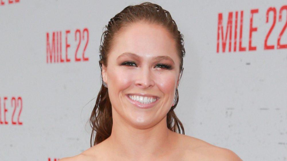Ronda Rousey souriant, avec ses cheveux lissés en arrière, à la première Mile 22