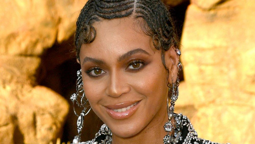Beyoncé dans une tenue noire scintillante, souriant à la première de The Lion King