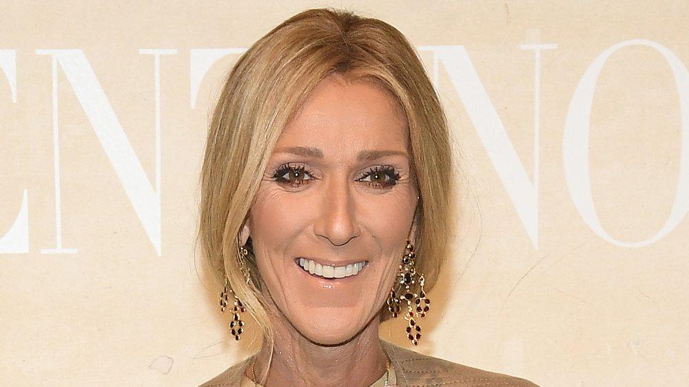 Céline Dion dans une tenue beige et boucles d'oreilles pendantes, souriant grande