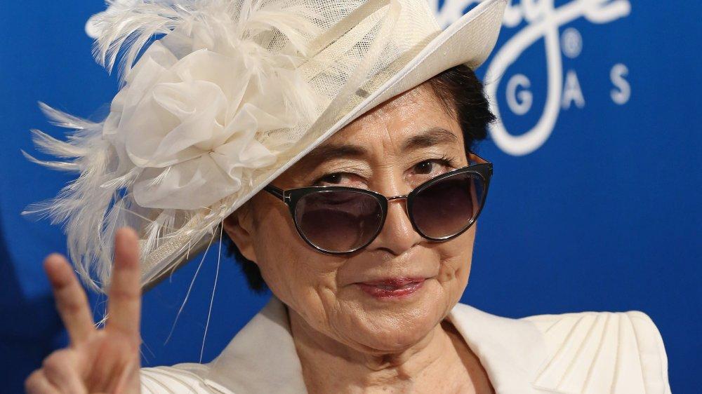 Yoko Ono dans un blazer blanc, chapeau, et lunettes de soleil, sourire et donner le signe de paix