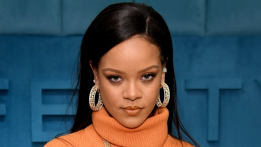 Rihanna dans une robe orange de cou de tortue, posant avec une expression sérieuse