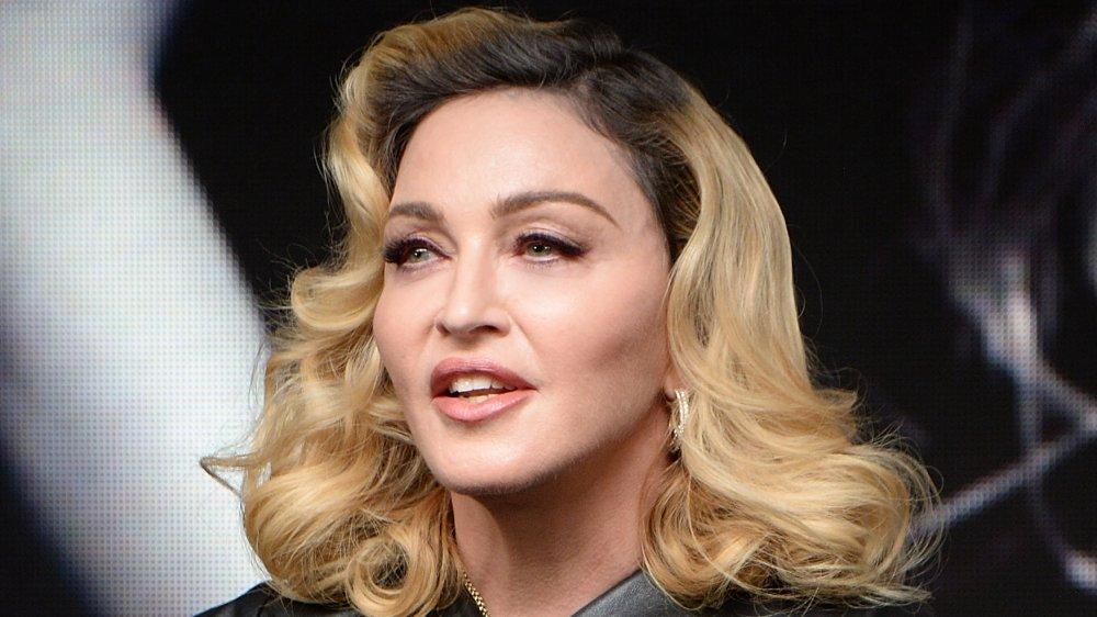 Madonna dans une tenue en cuir noir, parlant tout en regardant outre du côté