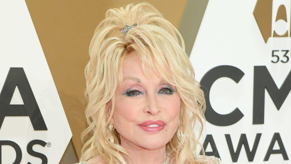 Dolly Parton dans une robe blanche scintillante, posant aux CMA Awards
