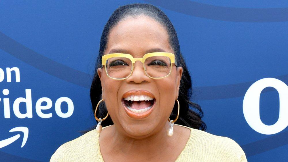 Oprah Winfrey dans une robe jaune et des lunettes, riant tout en regardant directement la caméra