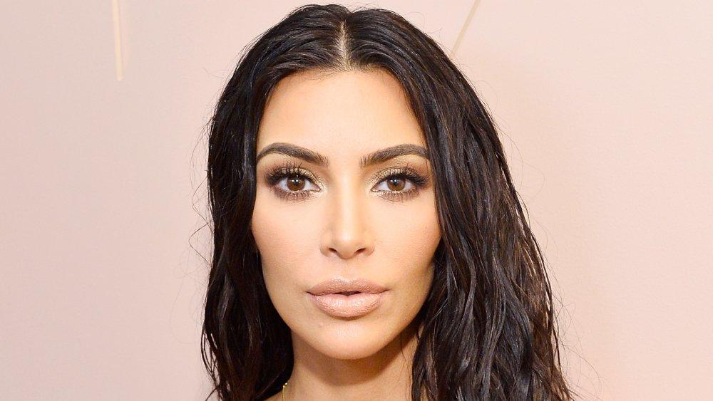 Kim Kardashian dans une robe blanche et le regard humide de cheveux, posant avec une expression étonnée