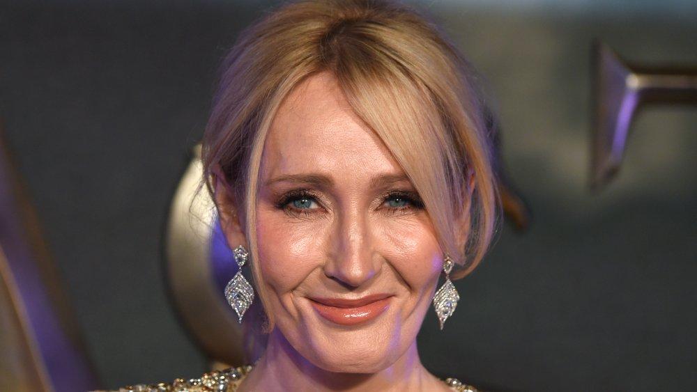 J.K. Rowling dans une robe scintillante d'or, souriant avec ses cheveux vers le haut