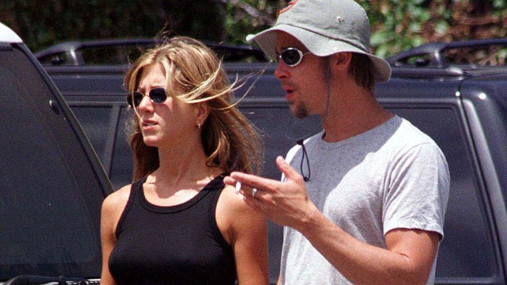 Jennifer Aniston et Brad Pitt, tous deux portant des lunettes de soleil, parlant tout en marchant dans un stationnement