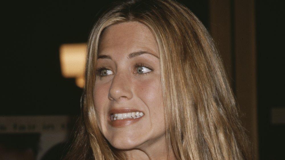 Jennifer Aniston grimaçant et haussant les épaules
