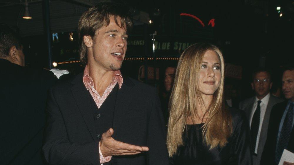 Brad Pitt et Jennifer Aniston, tous deux vêtus de noir, se tenant la main et marchant un événement tapis rouge