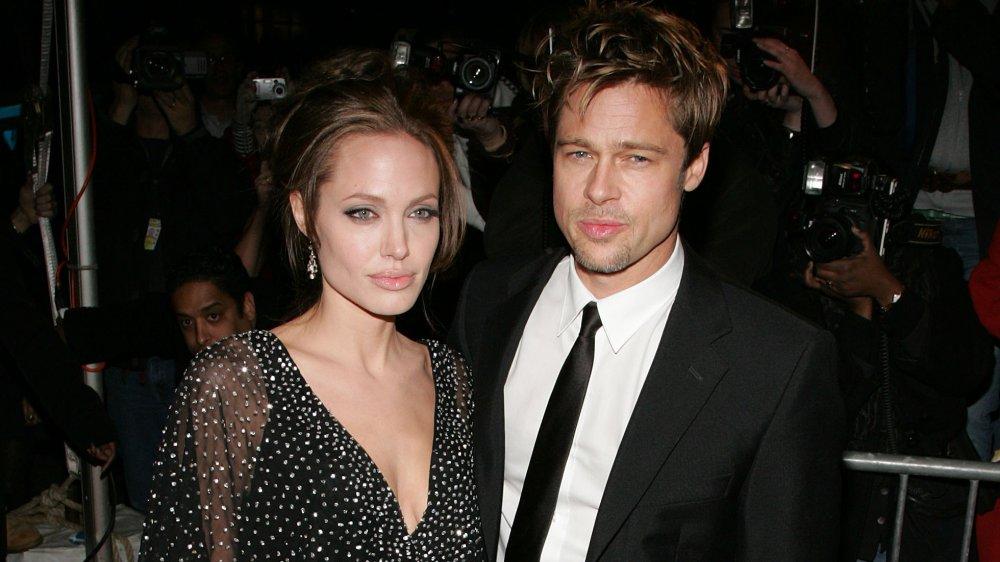 Angelina Jolie et Brad Pitt, posant avec des expressions sérieuses, entourés de photographes