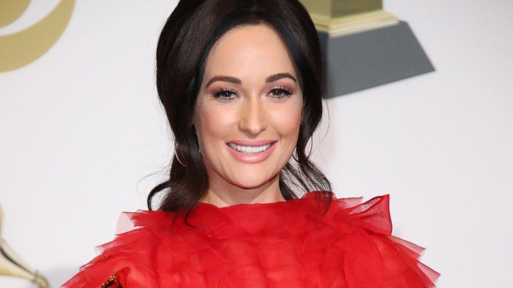 Kacey Musgraves dans une robe rouge et les cheveux tirés en arrière