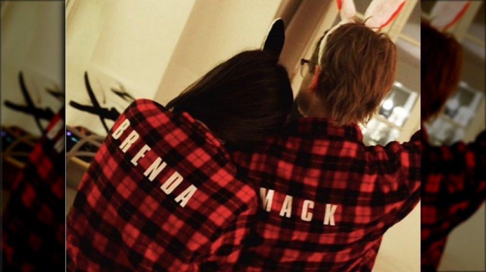 Brenda Song et Macaulay Culkin de l'arrière, portant des pyjamas à carreaux assortis