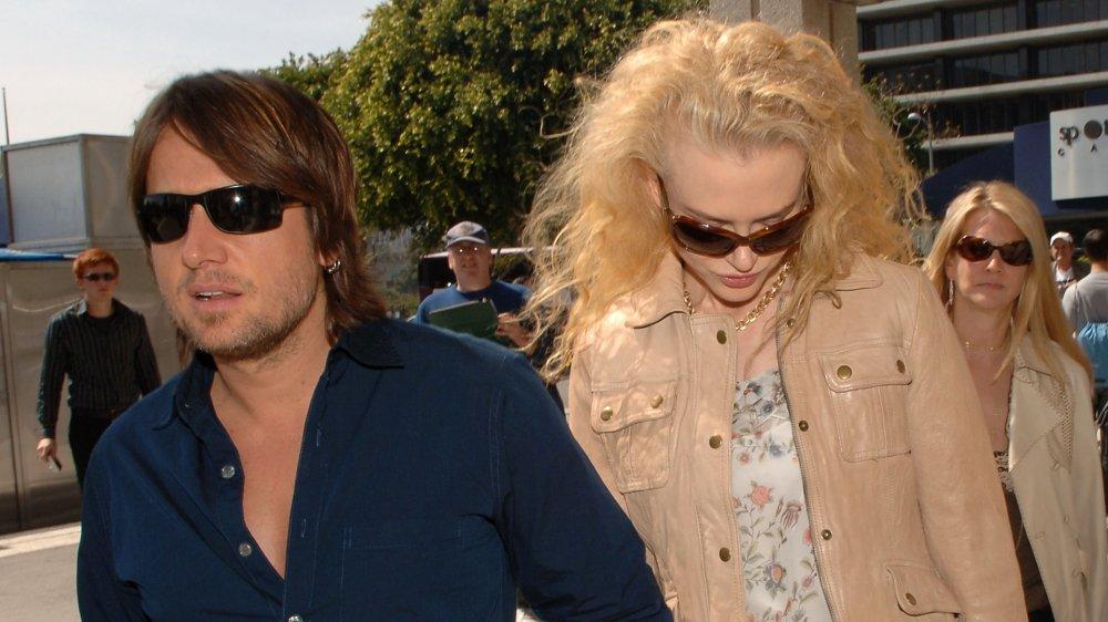 Keith Urban à la recherche sérieux, Nicole Kidman regardant vers le bas, les deux portant des lunettes de soleil