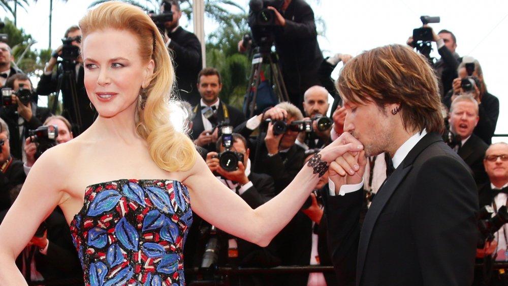 Keith Urban embrassant la main de Nicole Kidman lors d'un événement tapis rouge