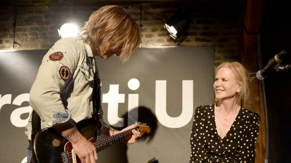 Nicole Kidman souriant tout en regardant Keith Urban jouer de la guitare