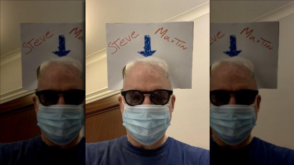 Steve Martin dans son masque avec un signe sur sa tête