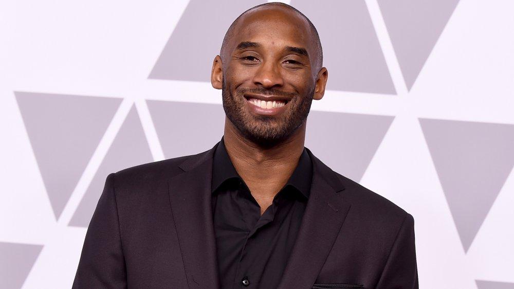 Kobe Bryant dans un costume tout noir, souriant