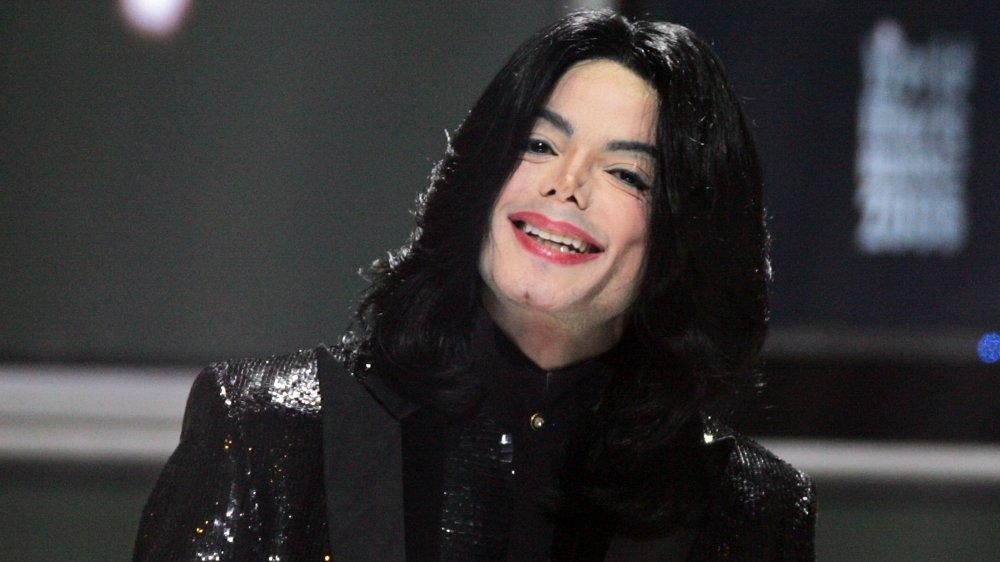 Michael Jackson dans un costume à paillettes noires, souriant