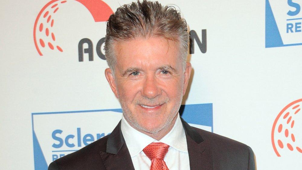 Alan Thicke souriant dans un costume et une cravate rouge