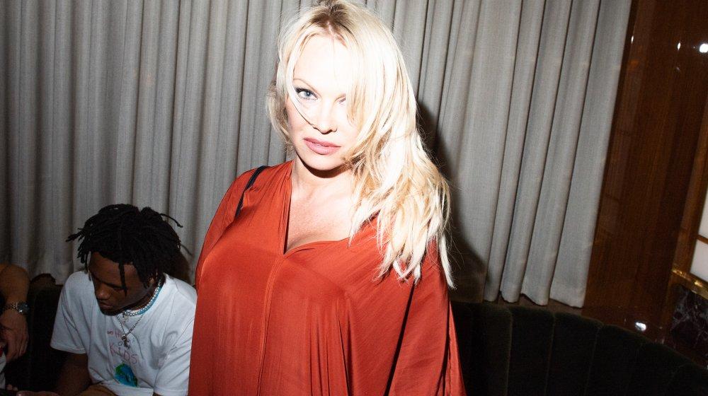 Pamela Anderson dans un haut rouge et cheveux blonds