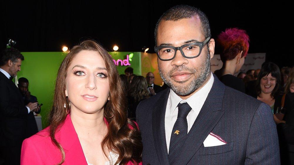 Chelsea Peretti dans un blazer rose, Jordan Peele dans un costume noir et bleu à rayures et des lunettes