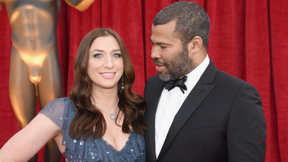 Chelsea Peretti souriant dans une robe bleue, Jordan Peele dans un costume noir regardant son