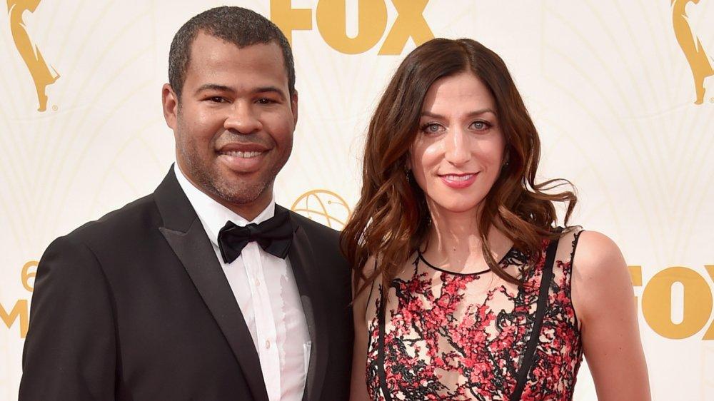 Jordan Peele en costume noir, Chelsea Peretti dans une robe noire et rouge