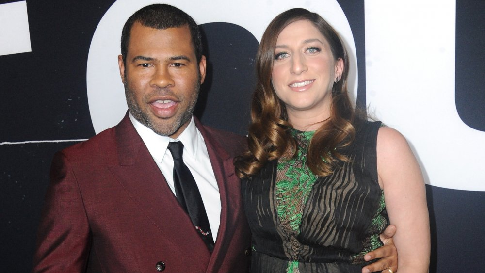 Jordan Peele en costume marron, Chelsea Peretti dans une robe verte et noire