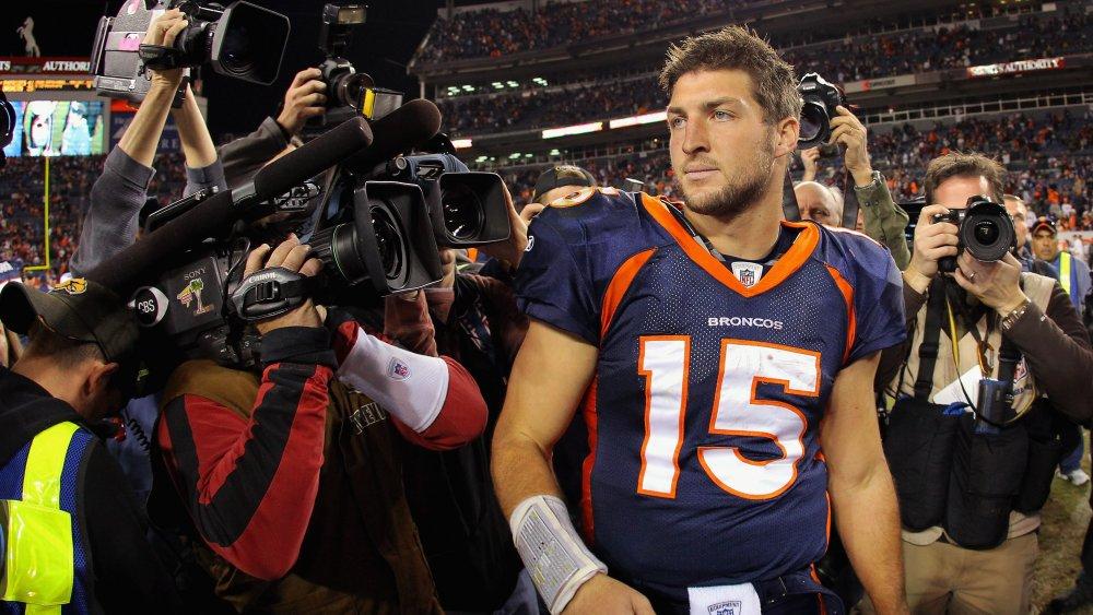 Tim Tebow dans un uniforme des Broncos de Denver, entouré de journalistes