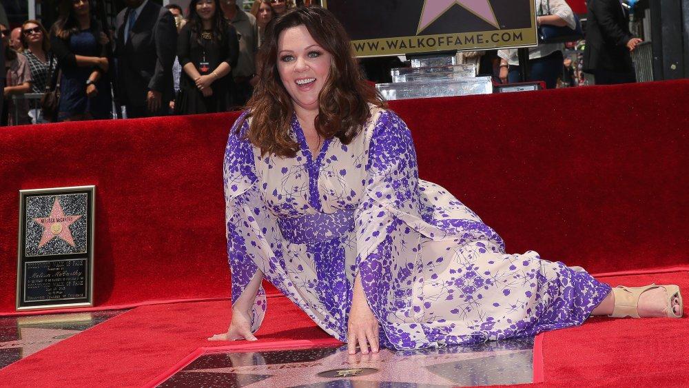 Melissa McCarthy assise à côté de son étoile sur le Hollywood Walk of Fame