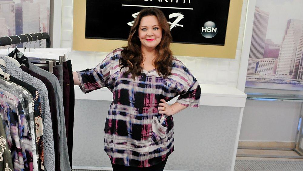 Melissa McCarthy posant à côté d'un porte-vêtements pour sa ligne de vêtements Seven7