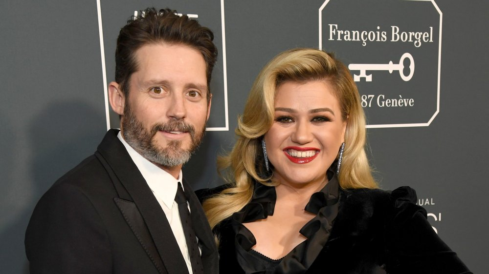 Brandon Blackstock et Kelly Clarkson, tous deux souriants tout en posant bras dessus bras dessous sur le tapis rouge