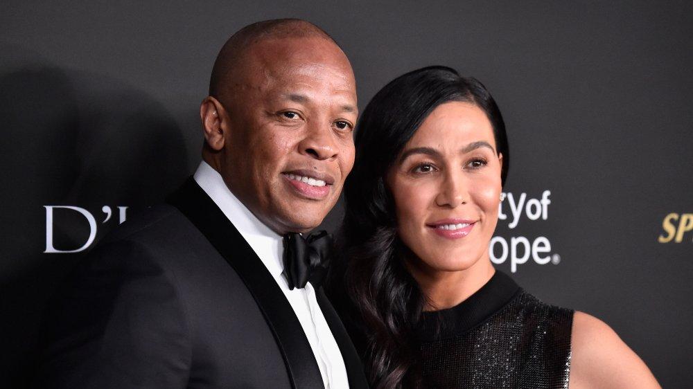 Dr Dre et Nicole Young, posant bras dessus bras dessous et souriant sur le tapis rouge