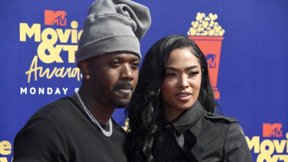 Ray J et Princess Love, vêtus de noir et posant bras dessus bras dessous sur le tapis rouge