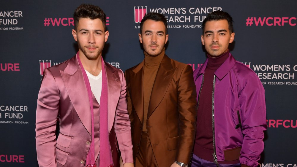 Les Jonas Brothers posant sur le tapis rouge