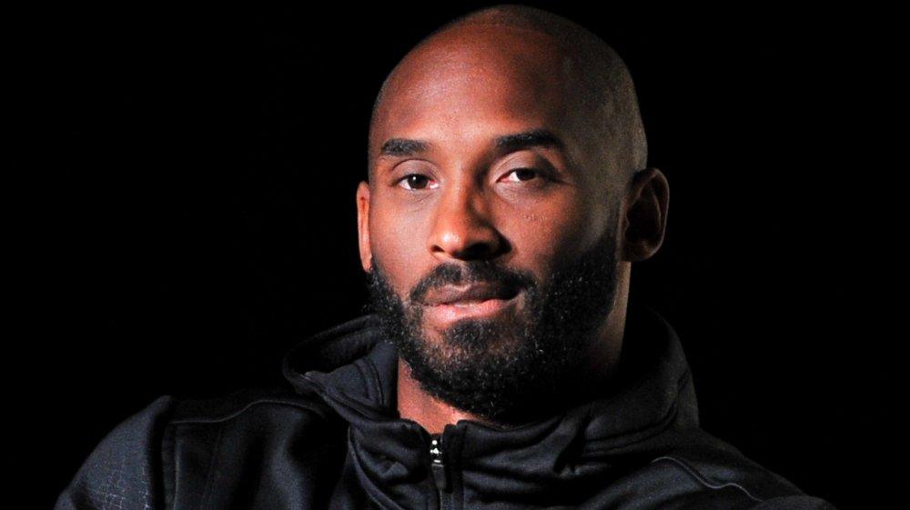 Kobe Bryant dans une veste noire regardant l'appareil-photo