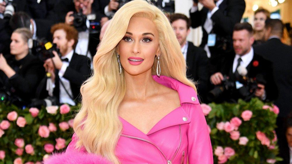 Kacey Musgraves avec cheveux blonds et veste en cuir rose chaud