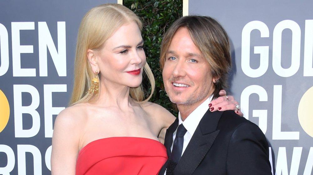 Nicole Kidman dans une robe rouge avec son bras autour de l'épaule de Keith Urban