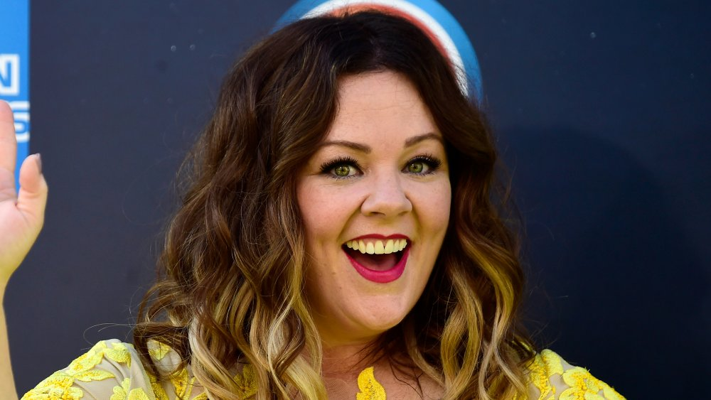 Melissa McCarthy dans une robe jaune, souriant grand et agitant