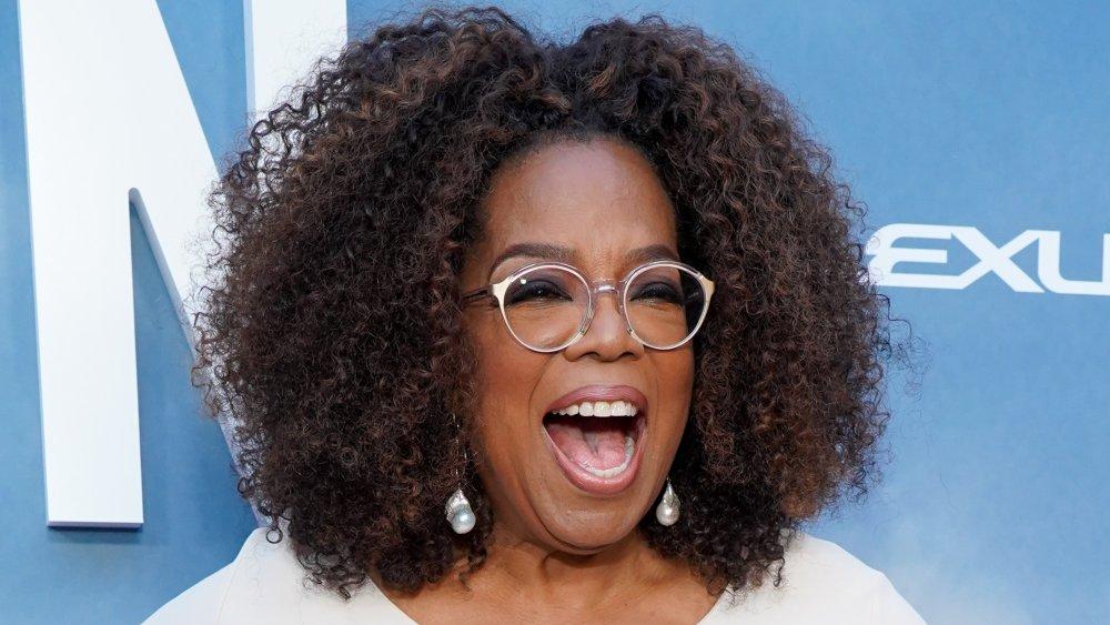 Oprah Winfrey dans une tenue blanche, riant sur le tapis rouge